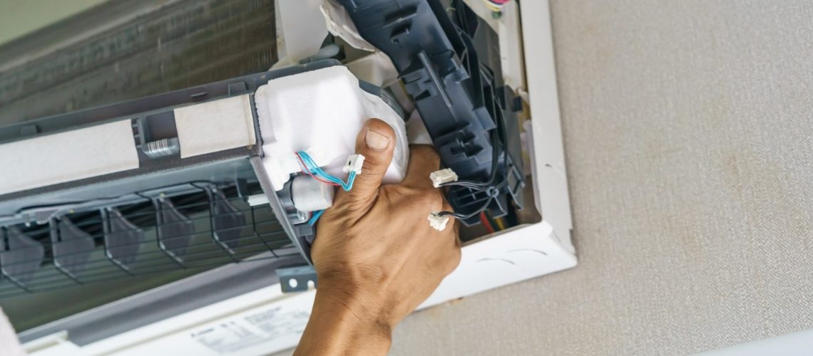Service technician is cleaning, repair and maintenance of air conditioner
