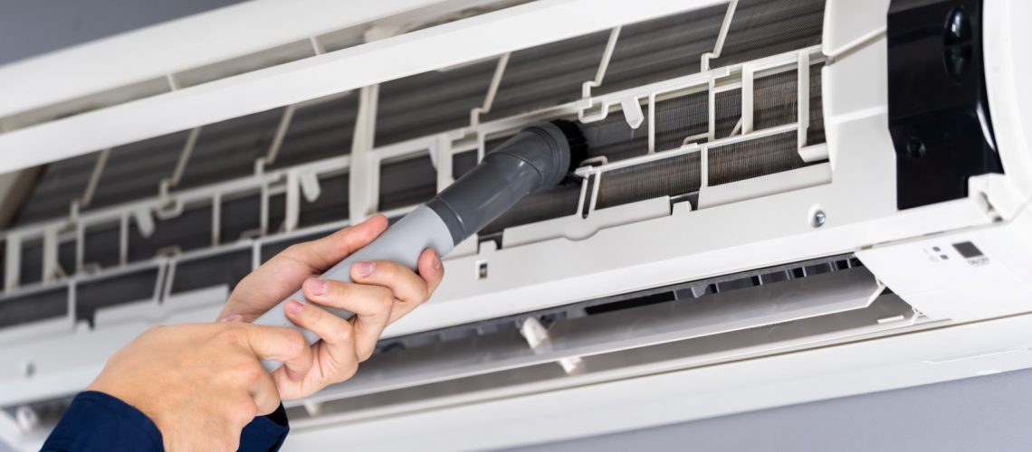 close up technician service using vacuum cleaner to cleaning the air conditioner