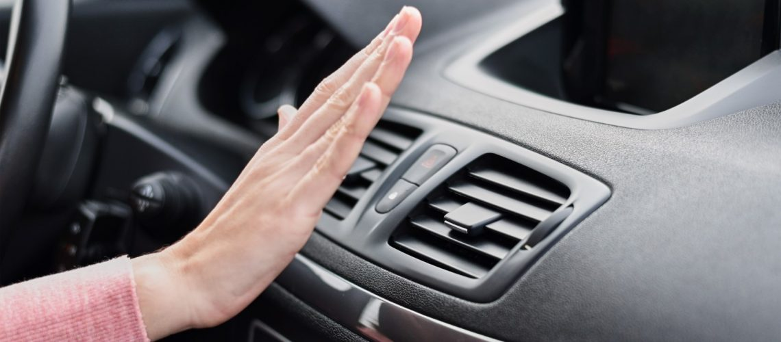 Woman hand on air conditioner ventilation grille in car. Climate control panel
