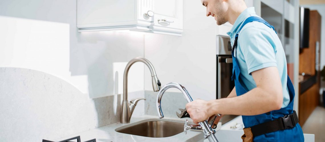 male-plumber-uniform-changes-faucet-kitchen-handyman-with-toolbag-repair-sink-sanitary-equipment-service-home